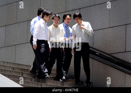 Group of Young Asian Businessmen Talkng and Walking Down Steps in Central, Hong Kong, China - Stock Photo