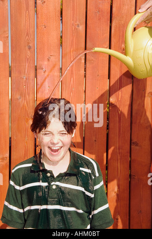 Watering can pouring over boy's head - Stock Photo