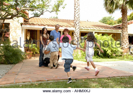a happy family in front of their house in the garden stock