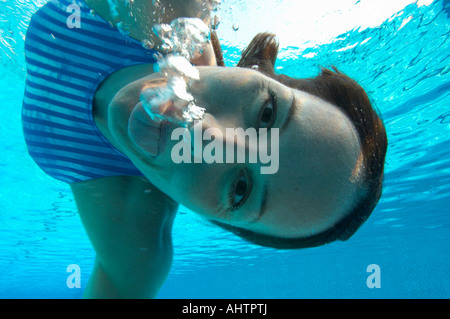 Female swimmer pulling face, portrait, underwater view - Stock Photo