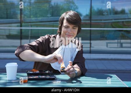 Smiling businessman eating sushi with chopsticks outside. - Stockfoto