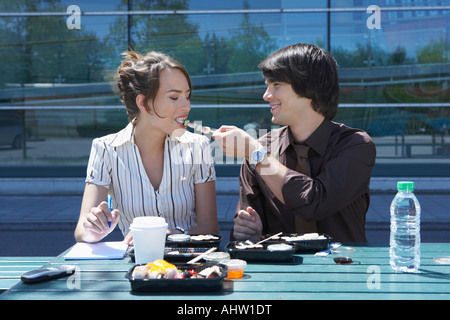 Couple eating sushi together outside while working. - Stock Photo