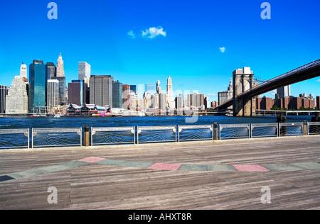 New York City skyline and Brooklyn bridge under blue sky - Stock Photo
