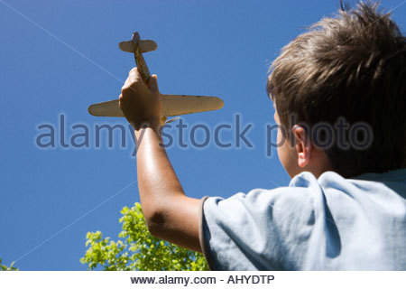 Boy 8 10 playing with toy plane in summer garden close up rear view low angle view - Stockfoto