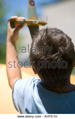 Boy 8 10 playing with toy aero plane in summer garden close up rear view - Stockfoto