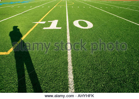Man casting shadow on American football pitch at 10 yard line - Stock Photo