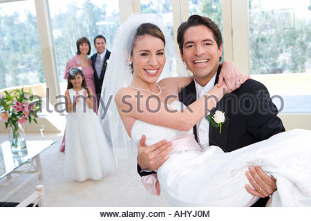 Groom carrying bride in arms at wedding, bridesmaid  and senior couple looking on, smiling, focus on foreground, - Stock Photo