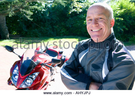 Senior man, in leather jacket, standing beside red motorbike on driveway, smiling, side view, portrait - Stock Photo