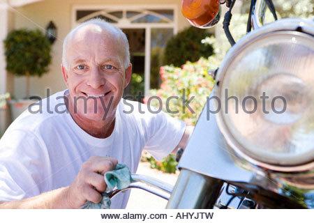 Senior man polishing motorbike on driveway, crouching down, smiling, close-up, portrait - Stock Photo