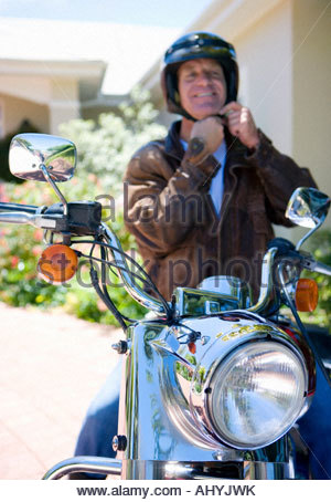 Senior man sitting on motorbike on driveway, adjusting crash helmet strap, smiling, front view, portrait - Stock Photo