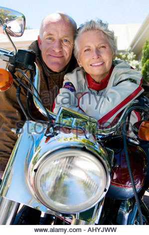 Senior couple sitting on motorbike on driveway, smiling, front view, close-up, portrait - Stock Photo