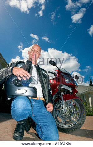 Senior man kneeling beside motorbike on driveway, holding crash helmet, smiling, portrait surface level - Stock Photo