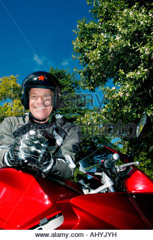 Senior man, wearing crash helmet and gloves, standing beside red motorbike on driveway, smiling, portrait, low angle - Stock Photo