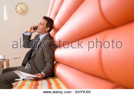 30's businessman talking on mobile phone sitting on red seats in office canteen, - Stockfoto