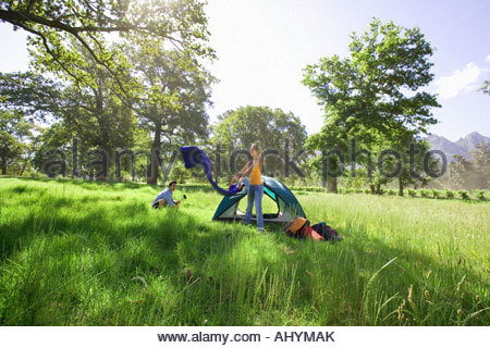 Young woman, in mid-distance, assembling dome tent on camping trip in woodland clearing, side view - Stock Photo