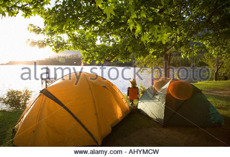 Young woman relaxing on camping trip near two dome tents beside lake at sunset, watching man standing on jetty in - Stock Photo