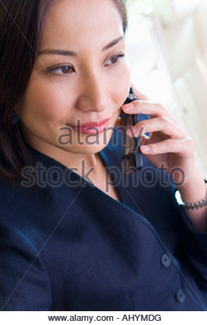 Businesswoman sitting in car, using mobile phone, smiling, close-up - Stock Photo