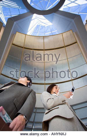 Businessman and woman standing below skylight in airport, woman using mobile phone, low angle view - Stock Photo