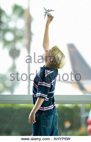 Blonde boy  playing with toy plane near large window in airport departure lounge, hand raised, profile - Stockfoto