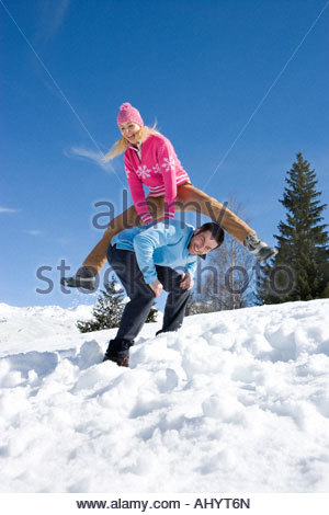 Young couple in snow field, smiling, portrait, woman jumping over man - Stockfoto