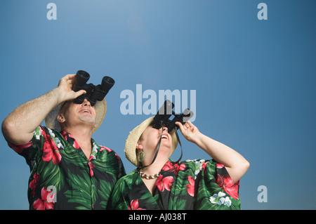 Senior couple looking through binoculars - Stock Photo