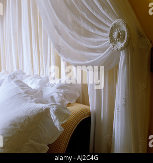 Closeup of bed corner with lace curtain and decorated holder in historic German stately home - Stock Photo