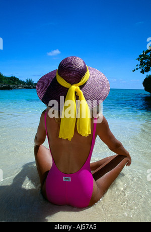 Grand Cayman Sandbar Woman in pink suit purple hat sits on the beach shot from behind - Stock Photo