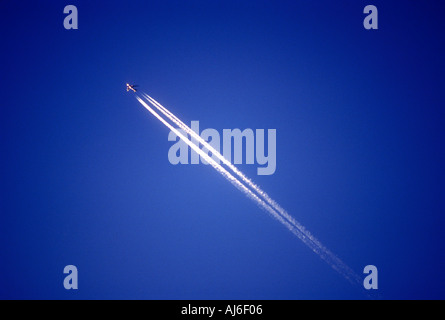 Commercial passenger airliner and vapor trail in sky - Stock Photo