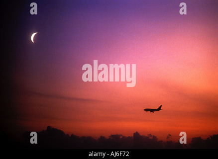 Commercial passenger airliner in flight at night with moon in sky - Stock Photo