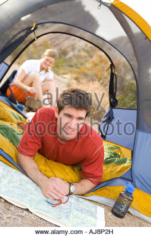 A smiling man looks at the map while at camp. - Stock Photo