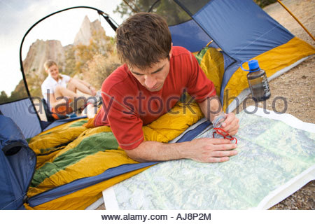 A man looks at map while at camp. - Stock Photo