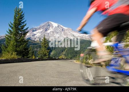 Young man mountain biking on road. - Stock Photo