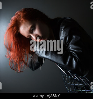 Pretty redhead young woman wearing leather jacket hanging over back of chair - Stock Photo