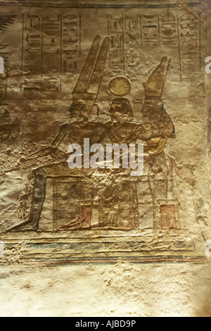Wall relief carving of holy triad of Luxor Thebes with Amun Ra sun god Ramsis II as Khonso moon god and Mut mother - Stock Photo