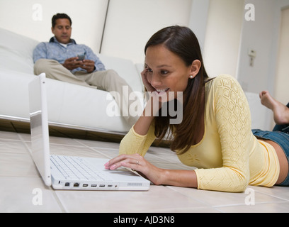 Woman lying on floor Using Laptop in living room, ground view - Stockfoto
