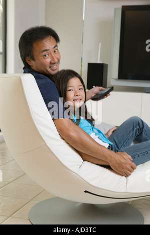 Father and Daughter preparing to watch television in living room, portrait - Stock Photo