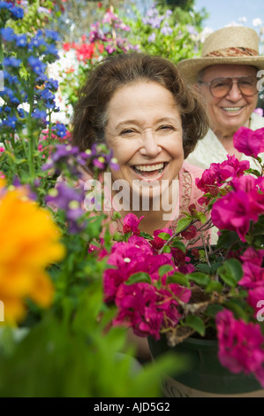 Senior Couple sitting in plant nursery seen through bed of flowers, portrait - Stock Photo