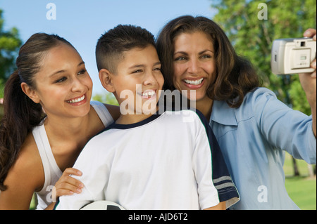 Mother using digital camera, photographing self with daughter and son (13-15). - Stock Photo