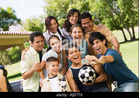 Young man using digital camera, photographing self with boy (13-15), friends, and family. - Stock Photo