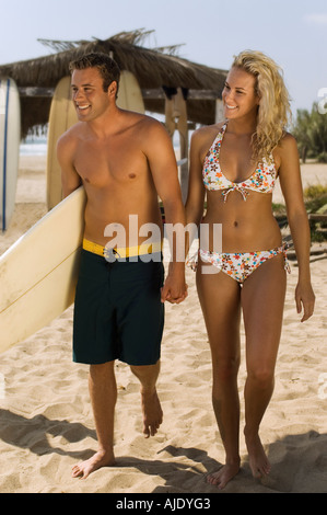 Surfer couple holding hands, carrying surfboard, walking on beach - Stock Photo