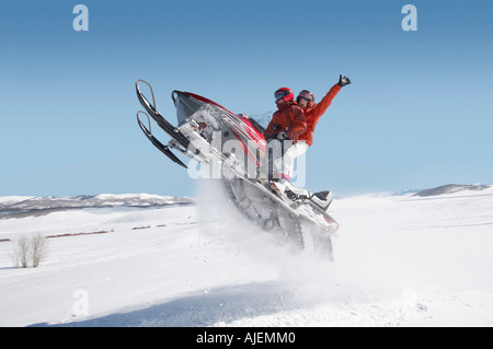 Couple jumping snowmobile in snow, mid air - Stockfoto