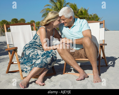 Affectionate senior couple on sunloungers on beach, holding hands - Stock Photo