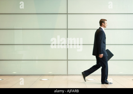 Businessman Striding Down Office Corridor, side view - Stock Photo