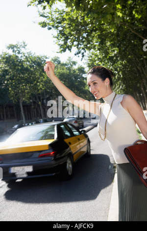 Businesswoman hailing taxi by road - Stock Photo