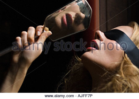 Blindfolded woman with a hand mirror - Stock Photo