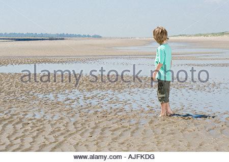 Boy standing on beach - Stock Photo