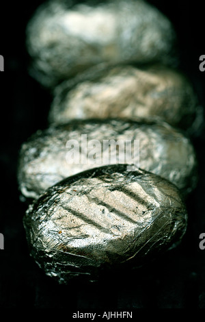 Potatoes wrapped in aluminium sizzling on the BBQ - Stock Photo