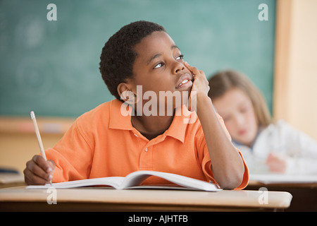 Schoolboy daydreaming in classroom - Stock Photo