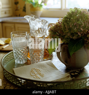 Refreshment tray with cut glassware, napkins and hydrangea in jug - Stock Photo
