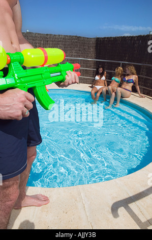 Man holding a water pistol - Stock Photo